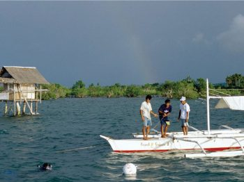 3 people in a boat, grey sky and rainbow behind them, fishing shack to the left, looks like somewhere in Asia